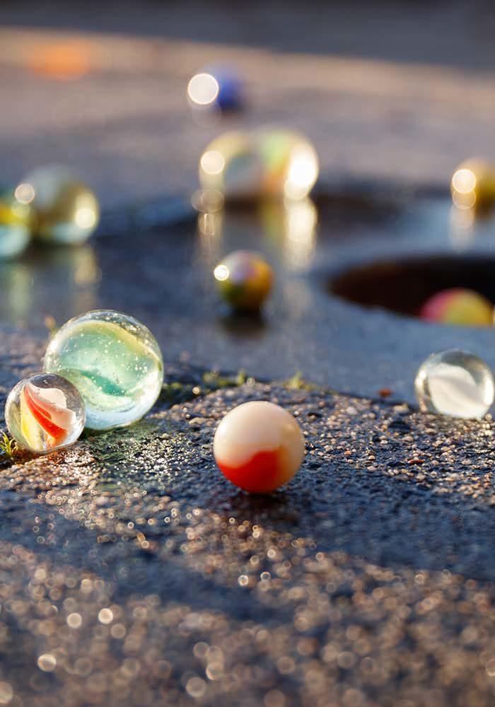 All kinds of colored glass marbles in the light of the setting s